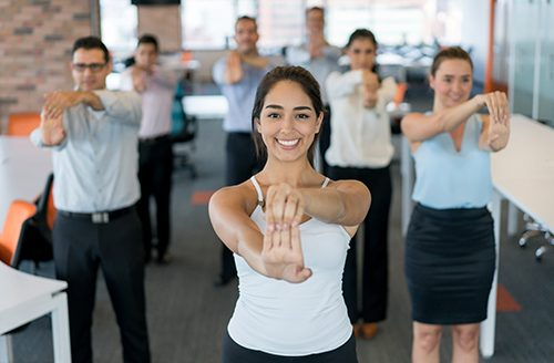 Business people on an active break at the office stretching and looking very happy - healthy lifestyle concepts